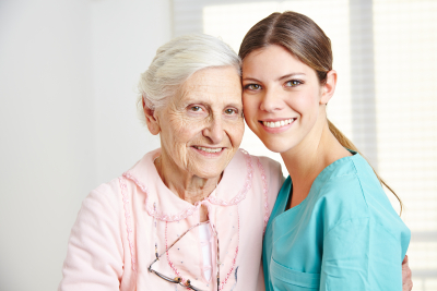 female caregiver and senior woman smiling